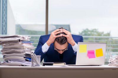 Mann mit zu viel Arbeit im Büro